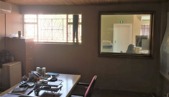 The image shows the old Vertical blinds still on the window before our installation of Venetian Blinds. The sun catches the window directly and fills the room with light.